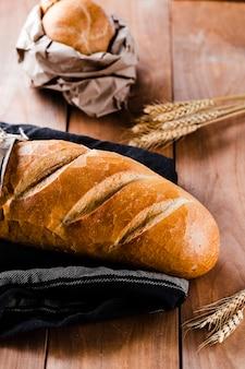 Высокий угол хлеба на деревянный стол