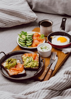 Высокий угол бутербродов на завтрак на кровати с жареным яйцом и тостами