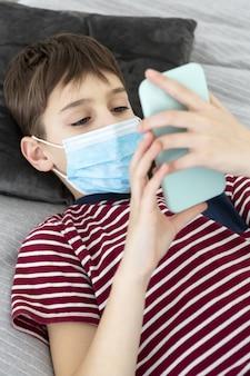 スマートフォンを保持している医療用マスクを持つ子供のハイアングル