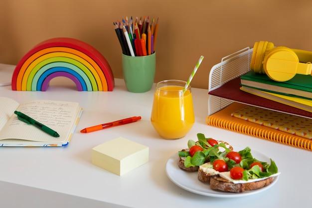 サンドイッチとオレンジジュースのある子供用デスクの高角度