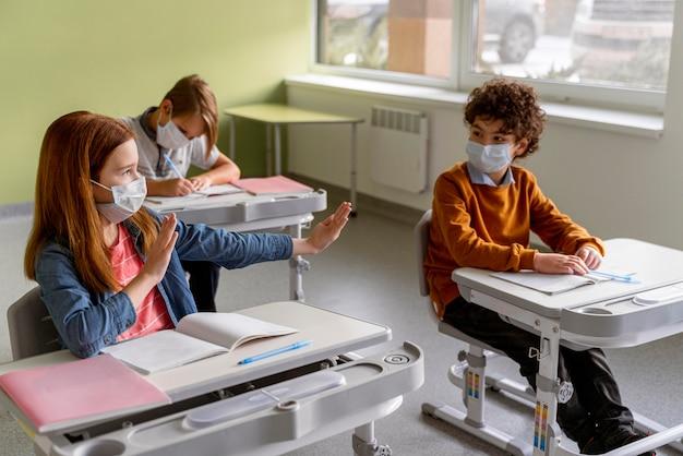 教室で距離を保つ医療用マスクを持った子供たちの高角度