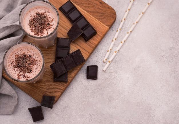 Высокий угол шоколадных молочных коктейлей с соломкой и копией пространства