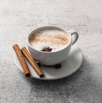 Высокий угол наклона кофейной чашки с палочками корицы и звездчатым анисом