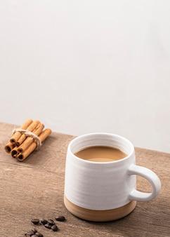 Высокий угол кофейной кружки с палочками корицы и копией пространства