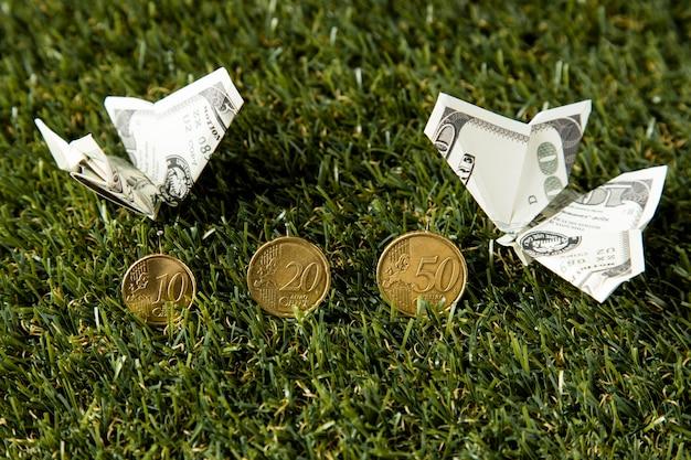 Высокий угол монет и банкнот в траве