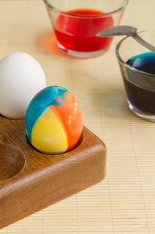 イースターのためのグラスとスプーンのペイントで着色された卵の高角度