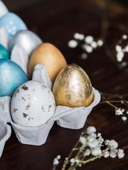 Высокий угол разноцветных пасхальных яиц в коробке с гипсофила