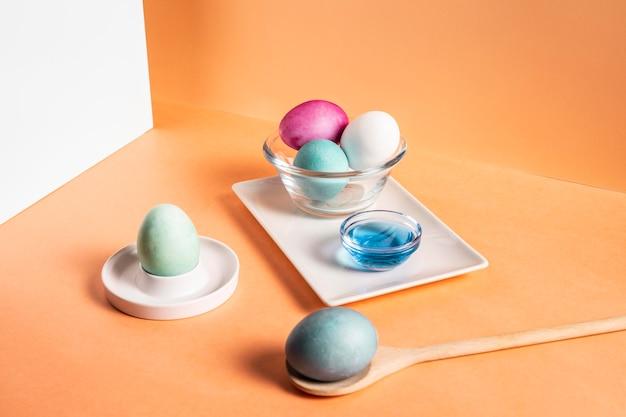 Высокий угол красочных окрашенных пасхальных яиц на тарелке с краской