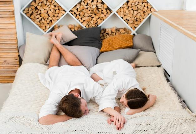 ベッドで寝ているバスローブのカップルの高角