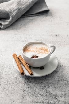 Высокий угол чашки кофе с палочками корицы