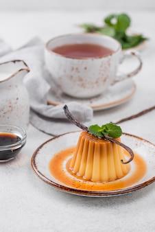 Высокий угол заварного крема на тарелке с мятой и стручком ванили
