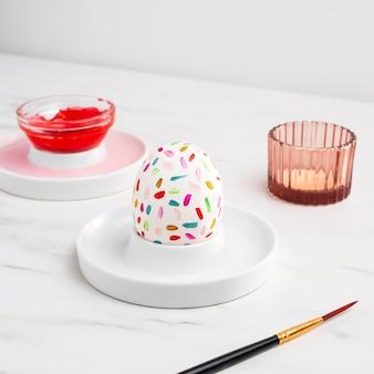 Высокий угол украшенного пасхального яйца на тарелке с краской и кистью