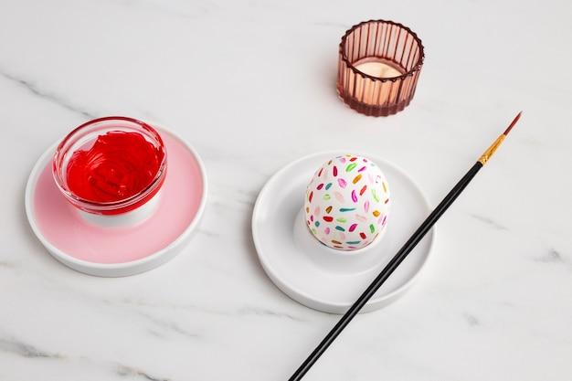 Высокий угол украшенного пасхального яйца на тарелке с кистью и краской