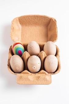 Украшенные пасхальные яйца в картонной коробке под высоким углом