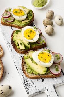 Высокий угол вкусных бутербродов с яйцом и авокадо