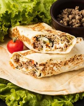 Высокий угол вкусного кебаба с мясом и салатом