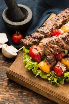 Высокий угол вкусного кебаба с мясом и овощами