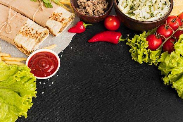 Высокий угол вкусного кебаба с помидорами и салатом