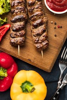 Высокий угол вкусного кебаба с овощами и кетчупом