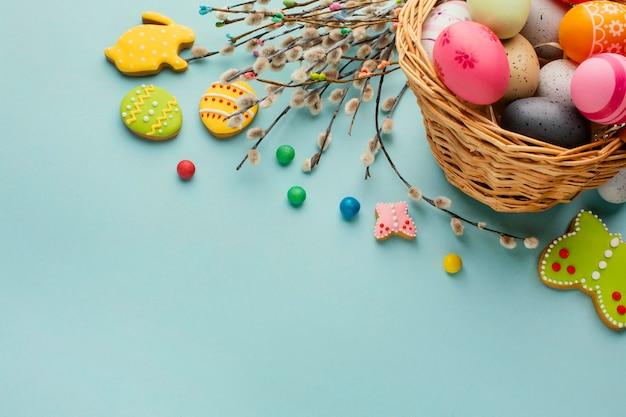 Высокий угол пасхальных яиц в корзине с фигурами кролика и бабочки