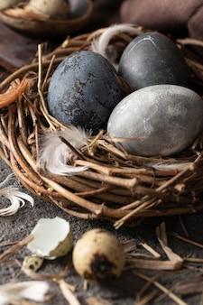 Высокий угол пасхальных яиц в птичьем гнезде из веток