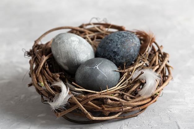 Высокий угол пасхальных яиц в птичьем гнезде с перьями