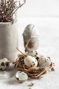 나뭇 가지에있는 부활절 달걀의 높은 각도는 꽃의 꽃병과 둥지