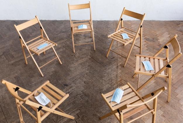 Высокий угол пустых стульев с медицинскими масками, подготовленными для сеанса групповой терапии