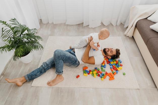 赤ちゃんと一緒に家の床で遊ぶ父親の高角度