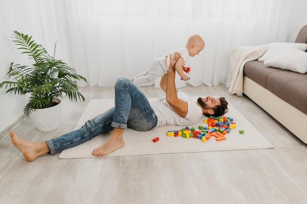 赤ちゃんと一緒に床で遊ぶ父親の高角度