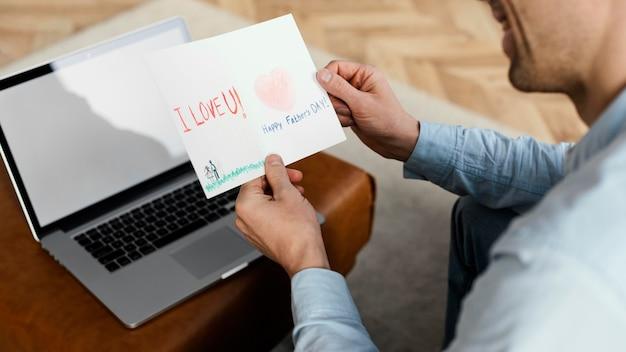 Под высоким углом отец читает дневную открытку своего отца во время работы на ноутбуке