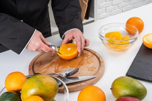 Высокий угол женского шеф-повара резки апельсина