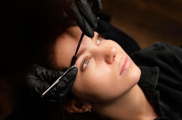 女性のお客様のために眉毛治療を行う女性臨床医の高角度