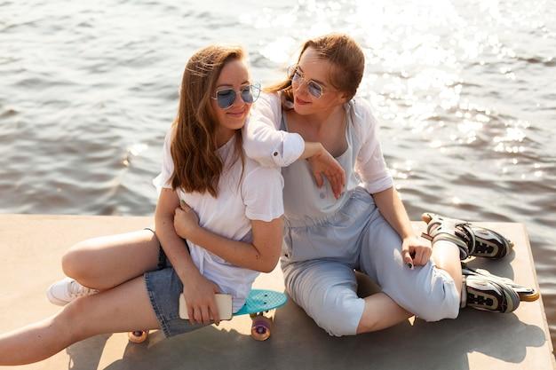 Подруги веселятся у озера под высоким углом