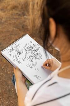 ノートに屋外でスケッチする女性画家の高角度