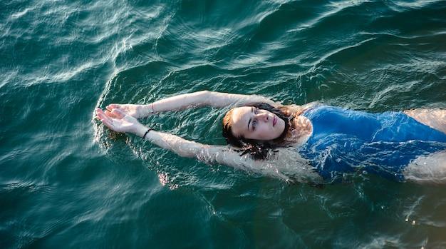 水に浮かぶ女性スイマーのハイアングル