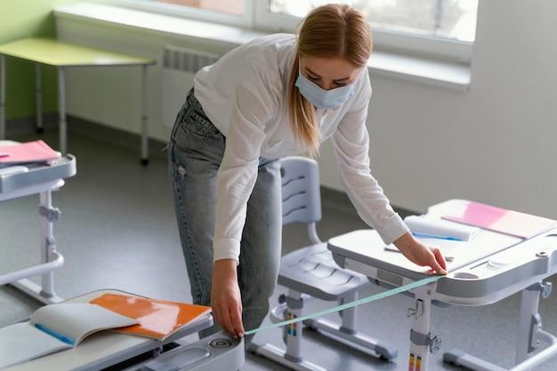 クラスのベンチ間の距離を測定する医療マスクを持つ女教師の高角度