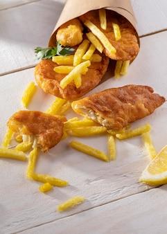 Блюдо из рыбы с жареным картофелем под большим углом в бумажном конусе