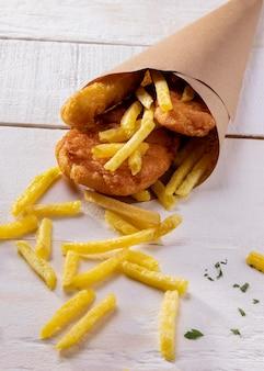 Рыба с жареным картофелем под большим углом в бумажном конусе