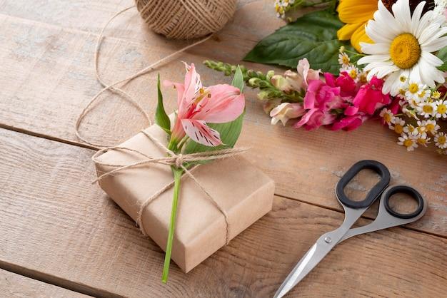 Высокий угол цветов с подарком и биркой