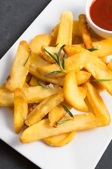 Высокий угол картошки фри с кетчупом и зеленью