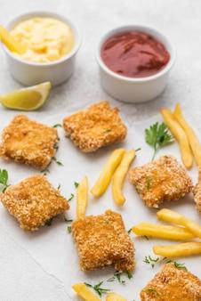 Жареные куриные наггетсы с соусом и картофелем фри под высоким углом