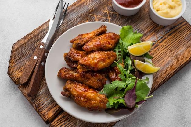 Высокий угол жареной курицы на тарелке со столовыми приборами и соусом