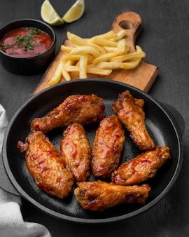 Высокий угол жареной курицы с картофелем фри