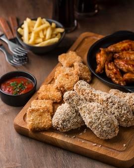 Высокий угол жареной курицы с соусом и картофелем фри