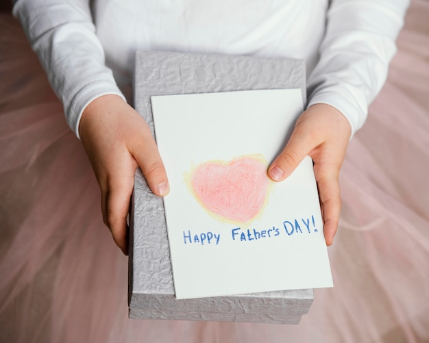 Высокий угол девушки, держащей подарок и открытку на день отца