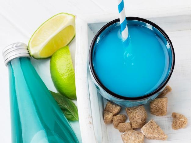 Высокий угол стакана безалкогольного напитка с бутылкой и соломинкой