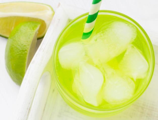 Высокий угол бокала безалкогольного напитка с лаймом и соломинкой