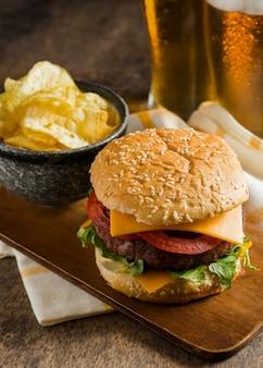 Высокий угол бокалов пива с чизбургером и чипсами