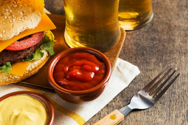 Высокий угол бокалов пива с чизбургером и соусом